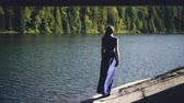 экологический : Beautiful young woman in long dress standing on shore near lake