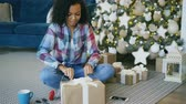 presente de natal : Attractive mixed race girl packing gift box near Christmas tree at home