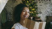 presente de natal : Young african american girl chatting online conversation using smartphone camera at home near Christmas tree Vídeos
