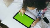 comunicações : Top view of curly mixed race woman lying in bed at home using electronic tablet with green screen