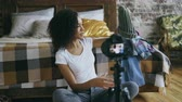 armário : Cheerful mixed race woman recording video blog about her wardrobe for travel with dslr camera at home