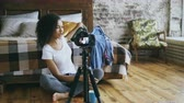 armário : Smiling curly african american girl recording video blog about her wardrobe for travel with dslr camera at home