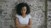 aborrecido : Portrait of angry curly mixed race woman looking into camera nervous on brick wall background