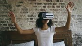 hitech : Young mixed race girl getting experience using VR 360 headset glasses of virtual reality at home