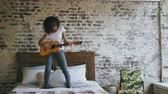 acústico : Mixed race young funny girl playing acoustic guitar and have fun dancing on bed at home Vídeos