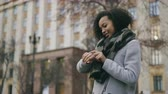 watch : Attractive african american student girl checking smartwatch and walking away near univercity