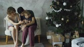 presente de natal : Happy family with cute little daughter sitting near Christmas tree and using smartphone at home Vídeos