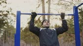puxando : Young athletic man doing pull-up exercise in winter park outdoors