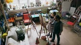 quadro : Skilled artist man teaching young woman painting on easel at art school studio - creativity, education and art people concept Stock Footage