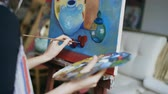artists canvas : Close-up tracking shot of artist woman with brush painting still life picture on canvas in art-class Stock Footage