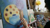 quadro : Woman artist smearing oil paints on canvas picture in art workshop