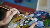pędzel : Close up of womans hand mix paints with brush in palette in art-class