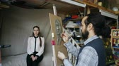 gesso : Skilled sculptor works with plasticine on canvas to create womans face of posing model in art studio