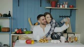 свадьба : Cheerful happy couple having online video chat using smartphone in the kitchen at home in the morning Стоковые видеозаписи