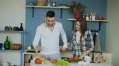 женат : Happy young couple in the kitchen. Attractive dancing man cooking while his girfriend come and help him in the morning