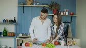 женат : Happy young couple in the kitchen. Attractive dancing man cooking while his girfriend help him in the morning
