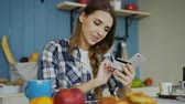 projeto de lei : Cheerful woman paying bills online using smartphone and credit card while have breakfast in the kitchen at home