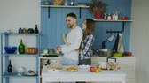 сумасшедший : Young joyful couple have fun dancing and singing while set the table for breakfast in the kitchen at home