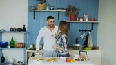 женат : Young joyful couple have fun dancing and singing while set the table for breakfast in the kitchen at home