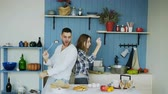 сумасшедший : Happy young couple have fun dancing and singing in kitchen while listening to music in the morning at home