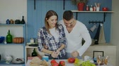 apple : Attractive loving couple having fun in the kitchen. Handsome man juggle with fruits to impress his girlfriend