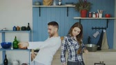 сумасшедший : Young joyful couple have fun dancing and singing while having breakfast in the kitchen at home on holidays