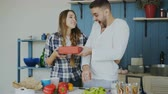 maravilhado : Laughing attractive woman surprising his boylfriend with a gift at home in the kitchen while he cooking breakfast
