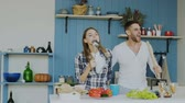 женат : Slowmotion of Young joyful couple have fun dancing and singing while set the table for breakfast in the kitchen at home