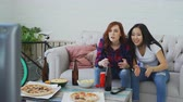 fãs : Two multi-ethnic female friends watching sports match on TV together at home while drinking beer and eating snacks