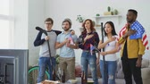 diverso : Multi ethnic group of friends sport fans listening and singing national USA anthem before watching sports championship on TV together at home Stock Footage