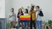 alemão : Multi ethnic group of friends listening and singing German national anthem before watching sports championship on TV together at home