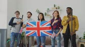 празднование : Multi ethnic group of friends listening and singing British national anthem before watching sports championship on TV together at home Стоковые видеозаписи