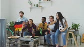 but : International young friends watching sport games match on TV together at home. Some of them happy about German team winning but Brazilian man disappointed
