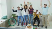 diverso : Happy young friends watching sports game on TV jumping and celebrating victory of favourite team at home Stock Footage
