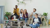 gritando : Group of happy friends watching sports game on TV at home. They cheering up favorite team and clapping hands Stock Footage