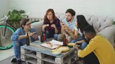 lanches : Group of young friends having home party and eating pizza taking it from table. Students talking and have fun Vídeos