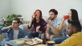 cerveja : Happy friends have party talking and eating pizza. They clink bottles sitting on sofa at home