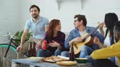 acústico : Happy young friends have party at shared apartment and singing together while their friend playing guitar at home Vídeos