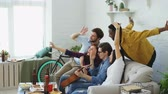 food photo : Multi ethnic group of cheerful friends taking selfie photos on smartphone camera while celebrating at party with beer and snacks at home indoors Stock Footage