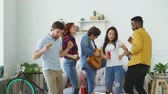 dyskoteka : Group of multi ethnic friends dancing and playing guitar while have home party