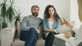 çözmek : Smiling couple listening and talking to professional psychologist and solve relationship porblems during visit psychotherapist office Stok Video