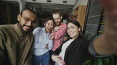 молодежная культура : Point of view of happy multi-ethnic team taking selfie in modern loft office. Woman holding smartphone and take self portrait together with her colleagues