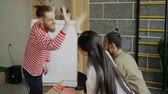мотивированы : Happy hipster man dancing and celebrating success of startup project and giving high five with multi ethnic team in modern office Стоковые видеозаписи