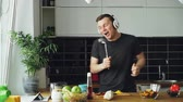сумасшедший : Attractive young funny man dancing and singing with ladle while cooking in the kitchen at home
