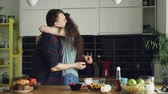maravilhado : Young man making proposal to his girlfriend while she cooking in the kitchen at home. He putting ring on her finger and kissing her