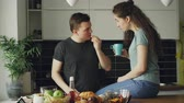 два человека : Happy young couple cooking ant talking in the kitchen at home. Attractive man feeding his girlfriend while cutting vegetables for breakfast in the morning