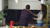 sedutor : Cheerful and attractive young couple in love dancing together funky dance in the kitchen at home on holidays