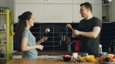 kepçeli : Happy couple having fun in the kitchen fencing with big spoons while cooking breakfast at home Stok Video