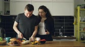 жена : young beautiful businesswoman came home from work ah home, her handsome husband is cooking in the kithcen, she is asking about dinner, they are kissing and laughing