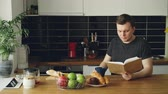 spacious : Portrait of young caucasian man sitting at table in modern spacious kitchen,reading book, drinking coffee, closing book and looking thoughtfuly through window
